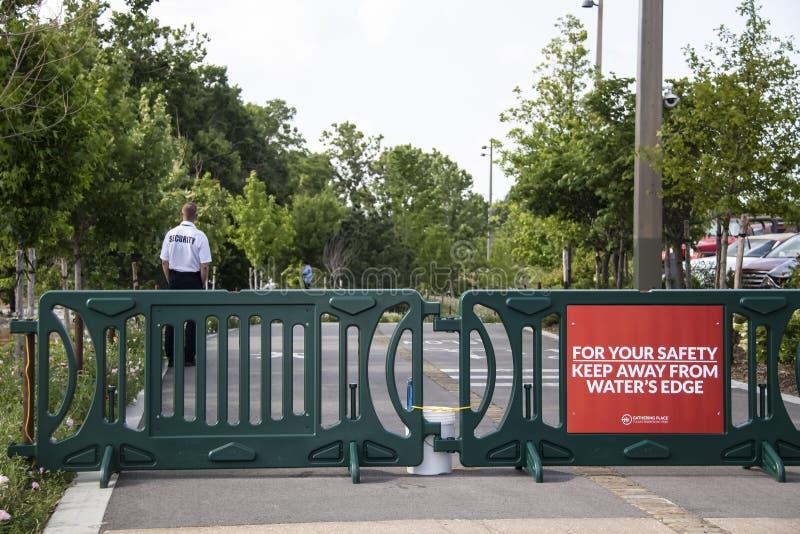 Pracownik ochrony utrzymuje ludzi od dostawać zbyt zamknięty woda powodziowa w Tulsa OK usa przy śladem Arkansas rzeką i chwilową obraz royalty free