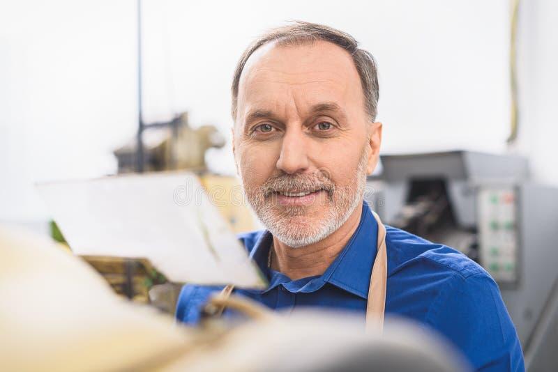 Pracownik ono uśmiecha się podczas gdy patrzejący kamerę zdjęcia royalty free