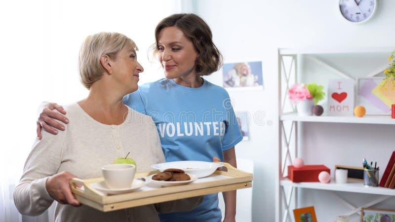 Pracownik opieki spo?ecznej kobiety mienia przytulenie przechodzi? na emerytur? taca z jedzeniem, zg?asza? si? na ochotnika wizyt obrazy stock