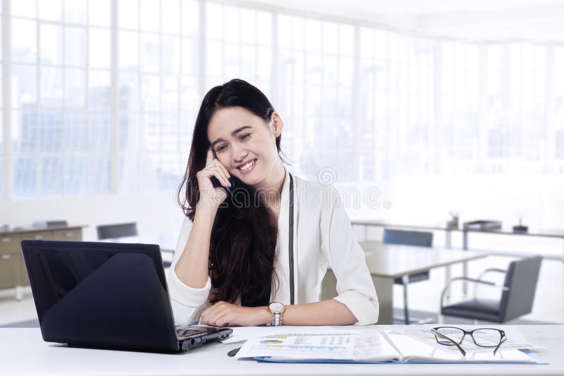 Pracownik opowiada na telefonie komórkowym w biurze zdjęcie royalty free