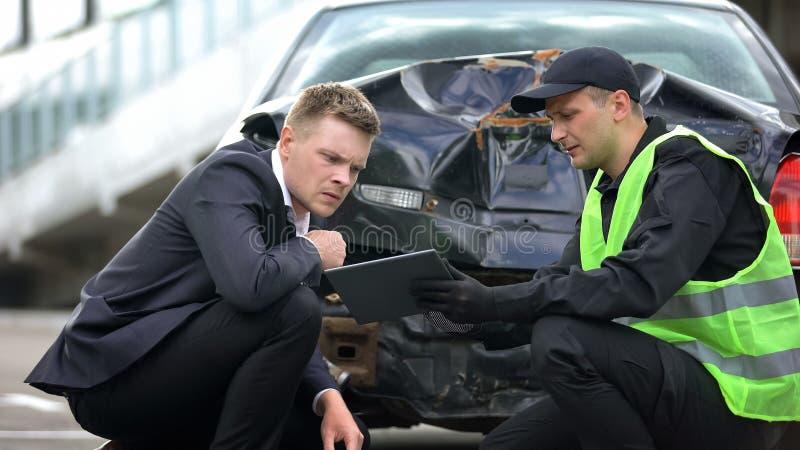 Pracownik patrolu pokazujący raport sterowników na tablecie online, nowoczesną technologię, wypadek zdjęcia royalty free