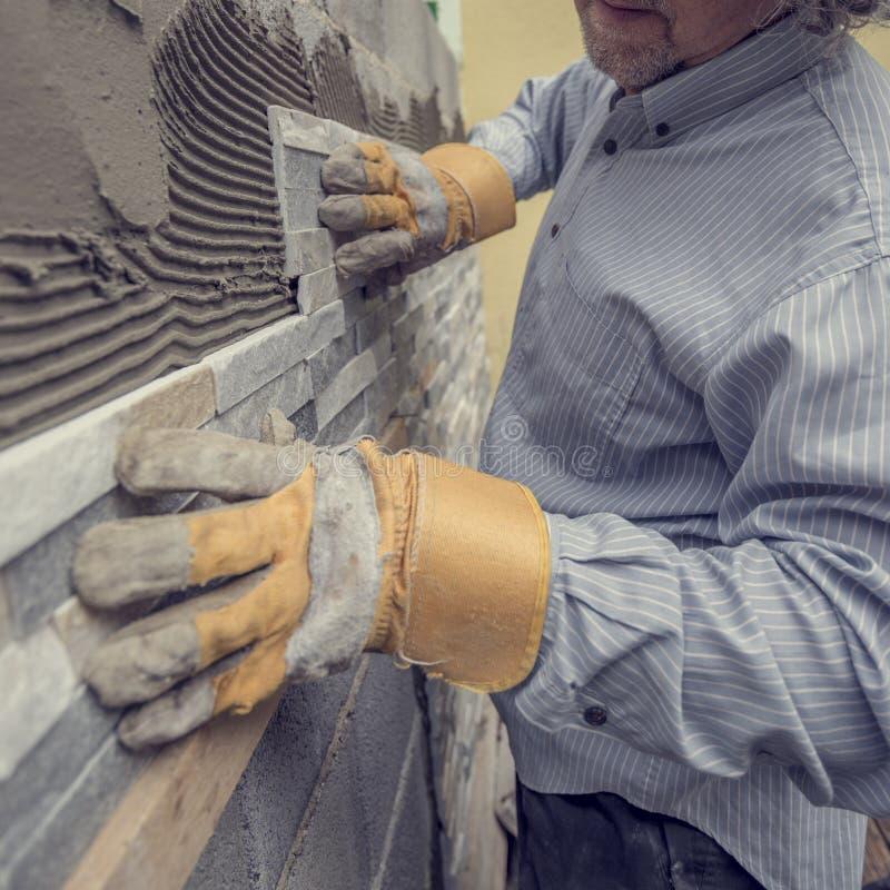 Pracownik pcha płytkę w cement na ścianie fotografia royalty free