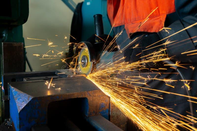 Pracownik piłuje metalu puste miejsce z tnącym kołem z szlifierską maszyną, wielkie iskry lata wokoło zdjęcie stock