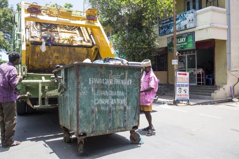 Pracownik przetwarzać śmieciarskiego poborcy ciężarówki ładowania kosz na śmieci i odpady fotografia royalty free
