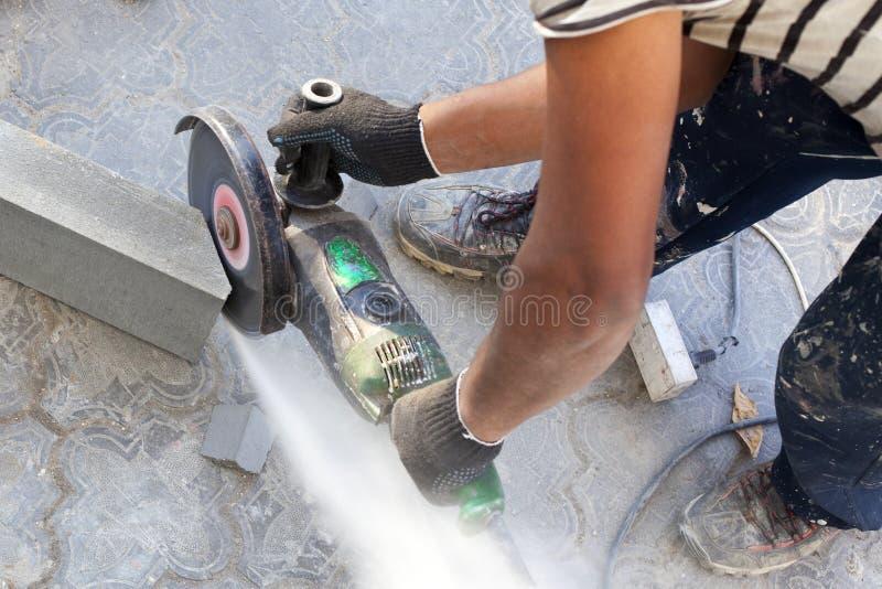 Pracownik przy budową piłuje kawałek betonowy krawężnik z kąta ostrzarzem, kółkowy elektryczny zobaczył, narzędzie w rękach mężcz obraz royalty free