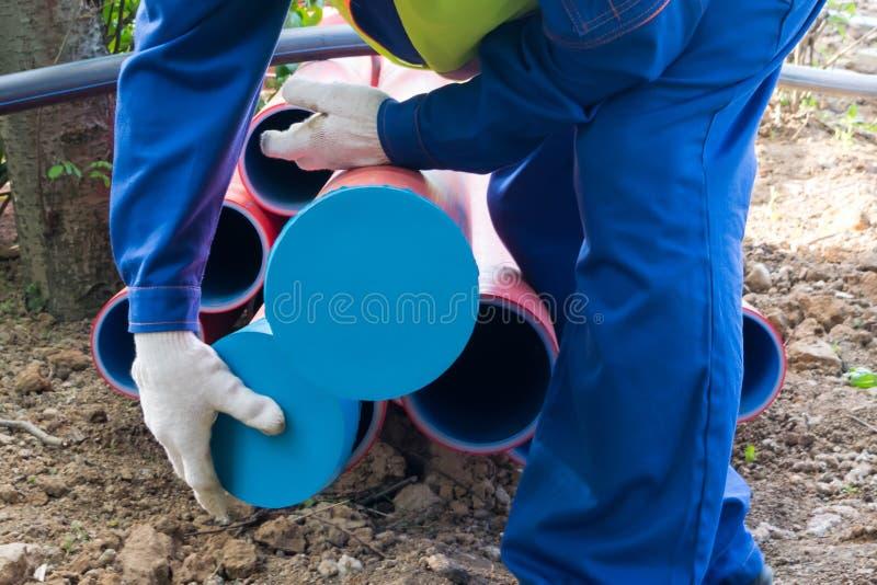 Pracownik przy budową zamyka końcówki drymby z nakrętkami, w górę obrazy royalty free
