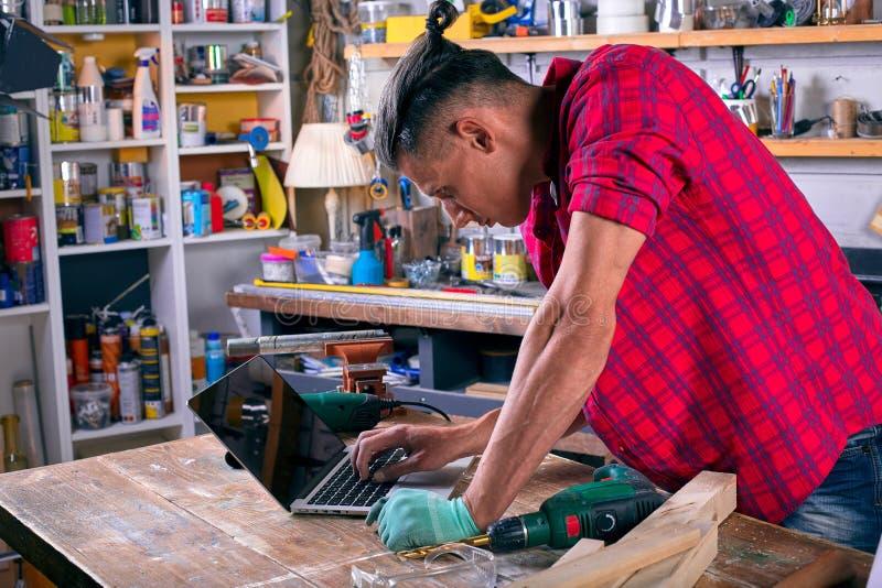 Pracownik przy jego miejsce pracy pracą z notatnikiem podczas gdy i stojący przy fabrycznym warsztatem zdjęcia stock