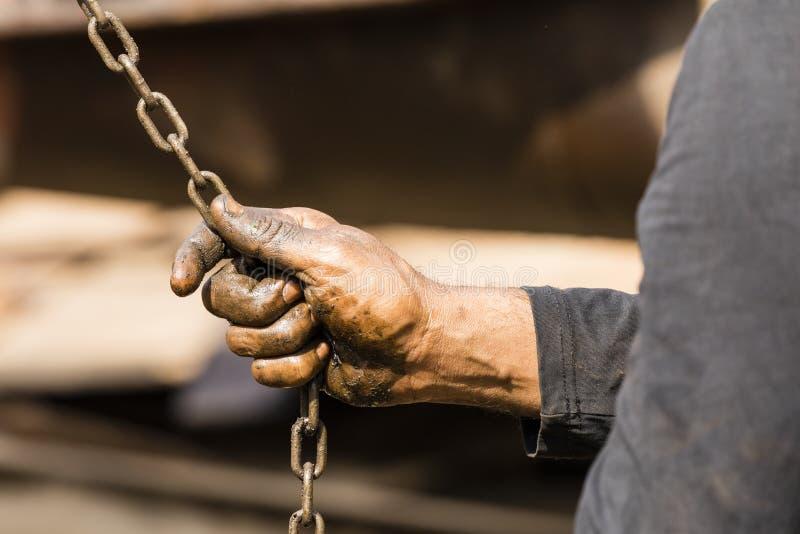 Pracownik przy stocznią w Dhaka Bangladesz trzyma łańcuch łańcuszkowy dźwignik z jego mazać rękami fotografia stock