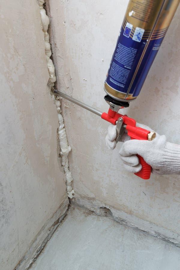Pracownik ręki dylemat czynsz w ścianie używać polyurethane pianę obraz royalty free