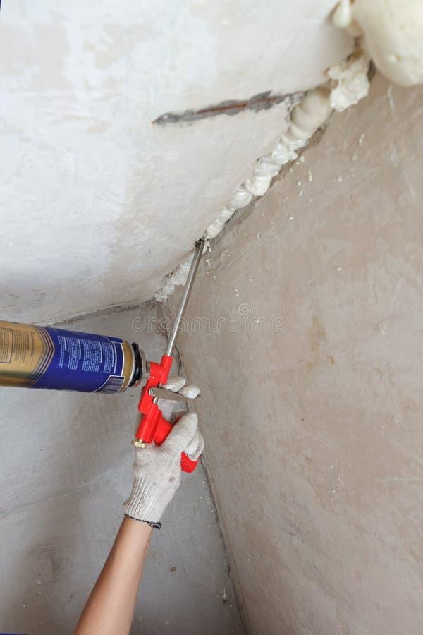 Pracownik ręki dylemat czynsz w ścianie używać polyurethane pianę obraz stock