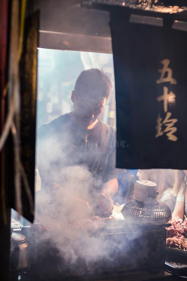 Pracownik restauracyjny narządzanie jedzenie dla klienta przy tradycyjnym barem w Omoide Yokocho, Shinjuku Portret orientacja zdjęcia stock
