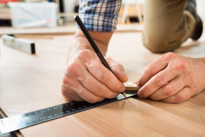 Pracownik rysuje ocenę na laminacie używać władcy zdjęcie royalty free