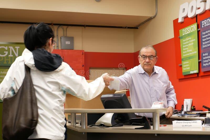 Pracownik sprawdza pakuneczek dla klienta przy urzędem pocztowym zdjęcie royalty free