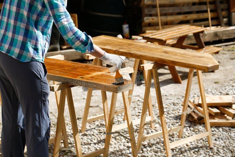 Pracownik stosuje świeżą drewnianą traktowanie farbę obrazy royalty free