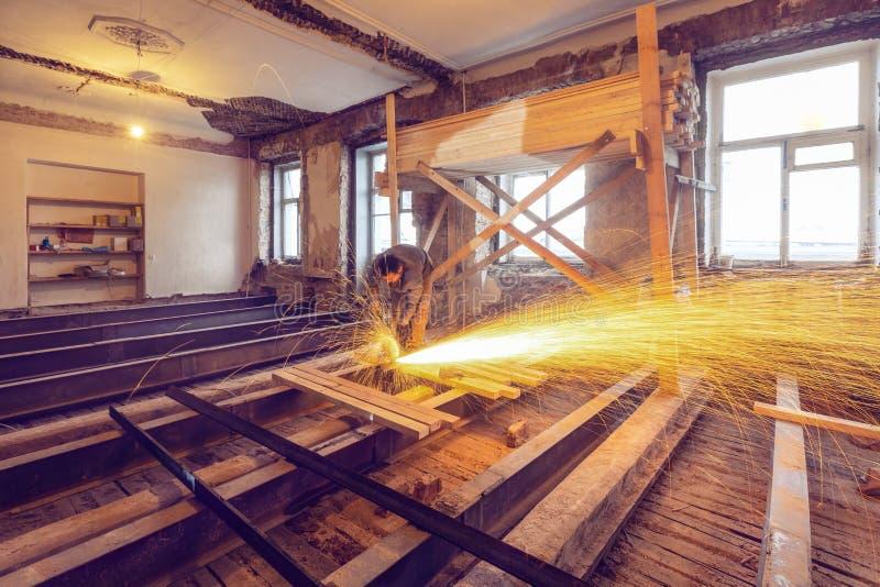 Pracownik używa kąta ostrzarza z fontanną przemodelowywa iskry w mieszkaniu który jest w budowie, odświeżanie zdjęcia royalty free