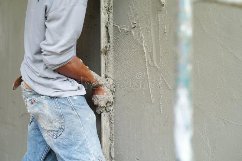 Pracownik używa kielnię dla gipsować brickwork ścianę mieszanym cementem obrazy royalty free