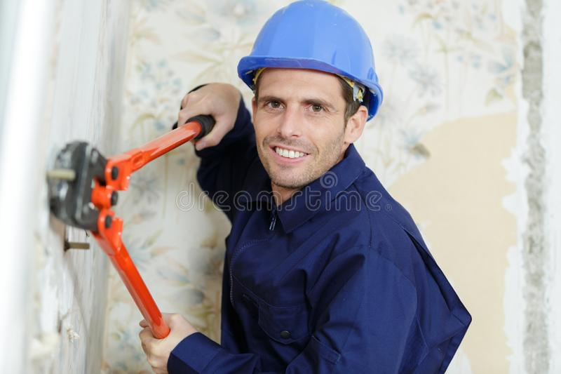 Pracownik używa nożyce na ścianie fotografia stock