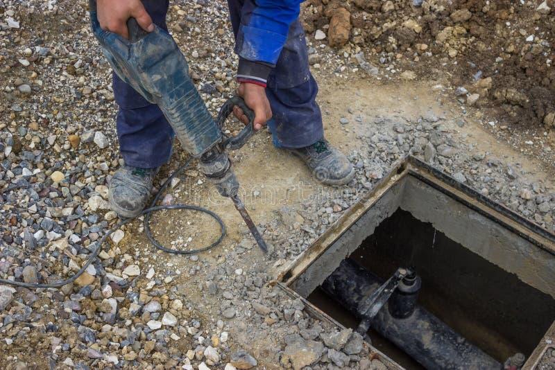 Pracownik używa perforator łamać up beton fotografia stock