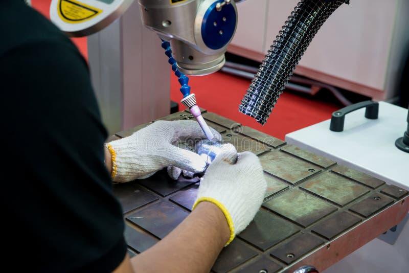 Pracownik używa remontową foremkę i kostka do gry rozdzielamy Laserową spawalniczą maszyną mnie zdjęcia royalty free