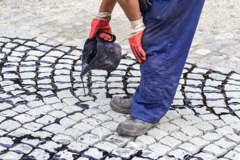 Pracownik używa smołowcowego wiadro i nalewający bitum w złącza zdjęcie royalty free