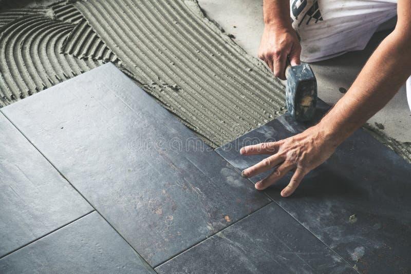 Pracownik umieszcza ceramiczne podłogowe płytki na adhezyjnej powierzchni obraz stock