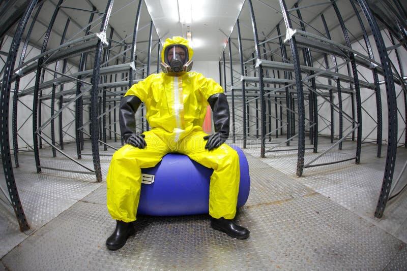 Pracownik w bezpieczeństwie - ochronny mundur, siedzi na błękit baryłce fotografia stock