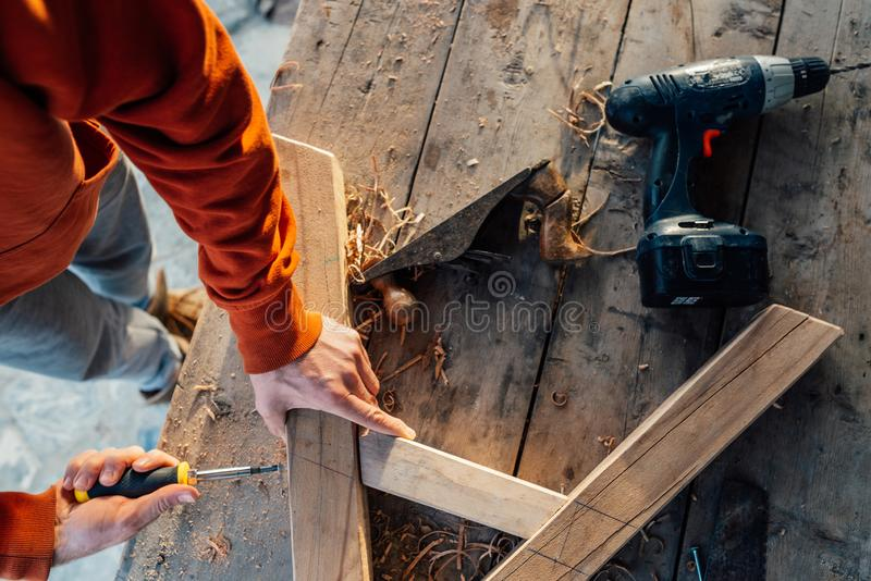 Pracownik w górę drewnianego poręcza z a z śrubokrętem na stole w trociny, zdjęcia stock
