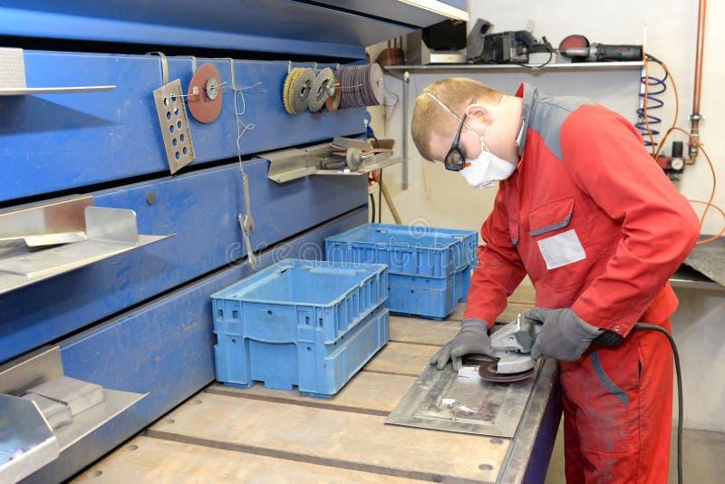 Pracownik w metalworking firmie sanding workpiece z szlifierską maszyną zdjęcie royalty free