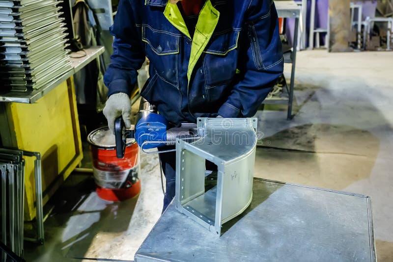 Pracownik w metalworking rośliny instalować w część dla budowa kanałów używać pneumatycznej nitarki nity obraz royalty free