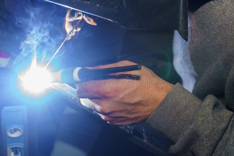 Pracownik w ochronnej maski spawalniczych stalowych poręczach indoors, iskry lata puszek obrazy stock