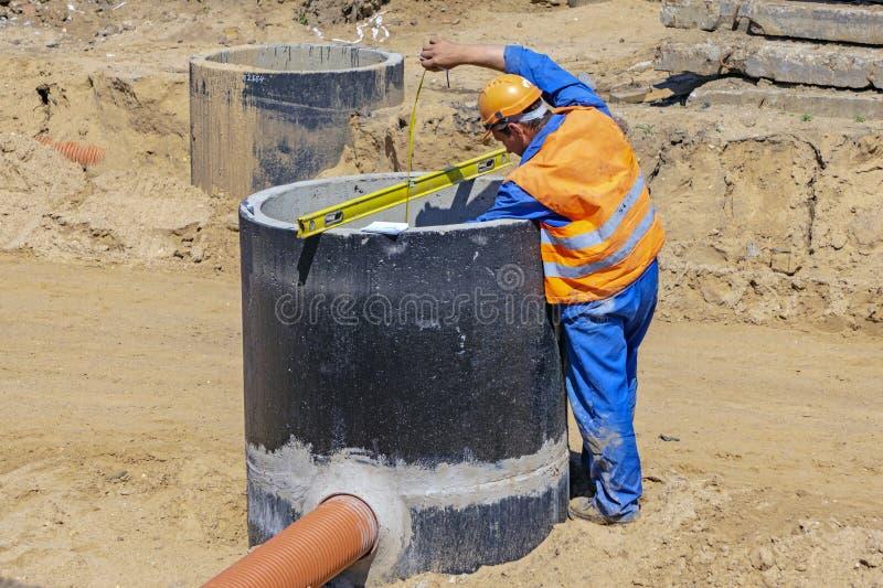 Pracownik w pomarańcze mundurze przy budową mierzy głębię beton dobrze fotografia royalty free