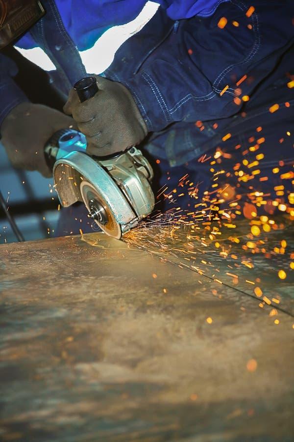 Pracownik w rękawiczkach i kombinezonach ciie metalu prześcieradło z śrutowanie maszyną Iskry latają od dyska przemysłowe tło fotografia royalty free