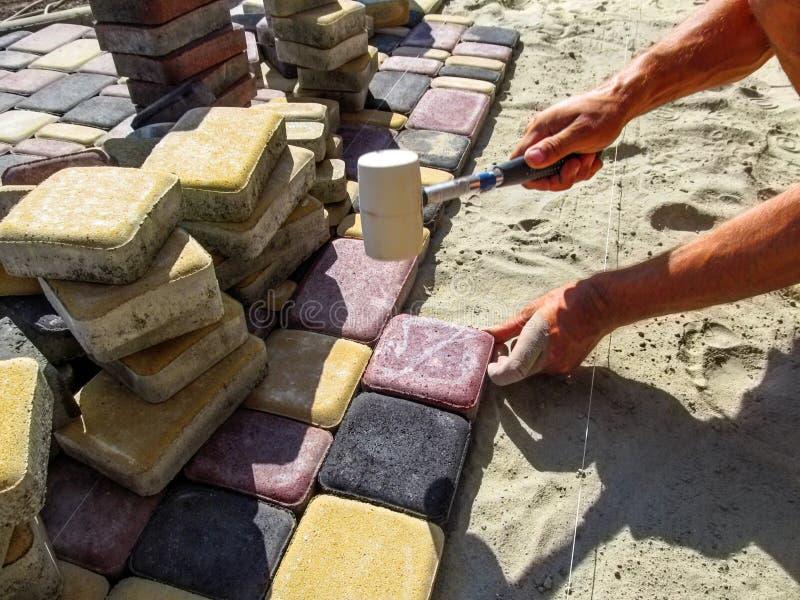 Pracownik w trakcie kłaść barwić brukowe cegiełki obraz stock