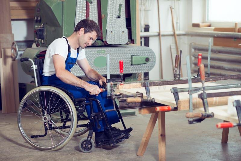 Pracownik w wózku inwalidzkim w cieśli warsztacie zdjęcia stock