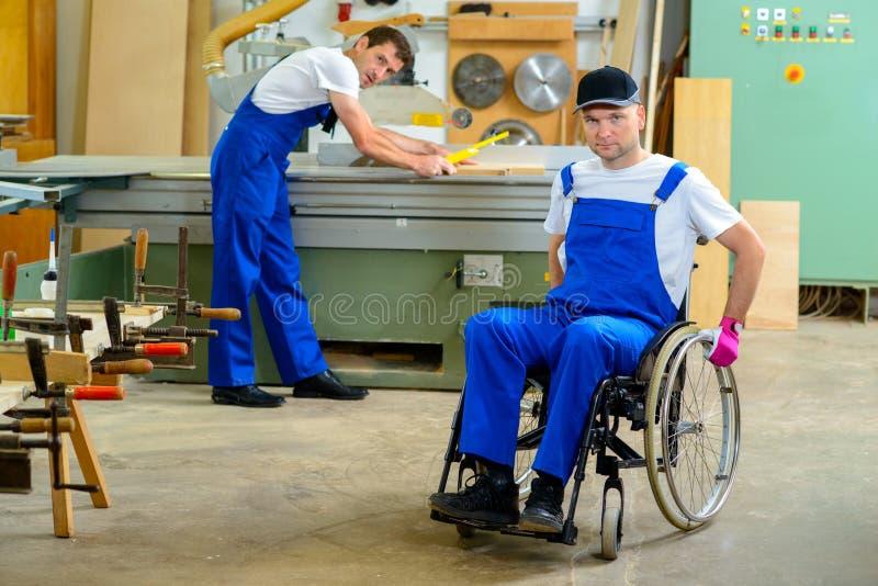 Pracownik w wózku inwalidzkim w cieśli warsztacie z jego colleagu fotografia royalty free