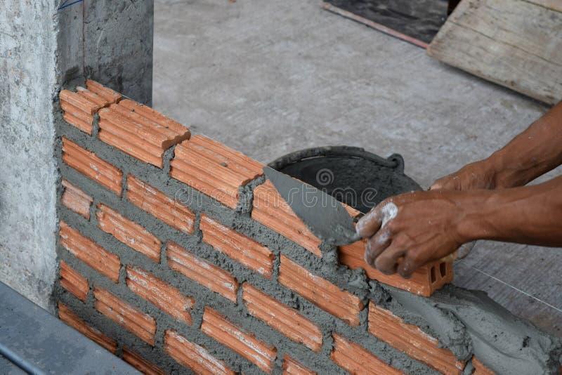 Pracownik w zakończeniu up przemysłowy murarz instaluje cegły i moździerz cementową cegłę zdjęcia royalty free