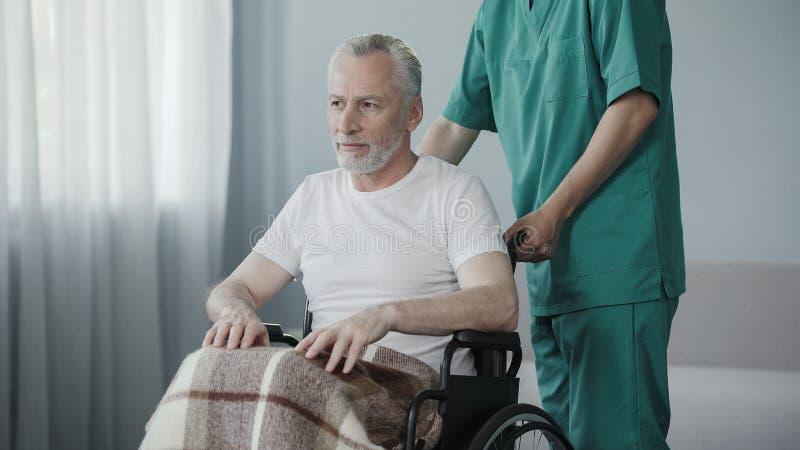 Pracownik wspiera starego chorego mężczyzna centrum rehabilitacji, radzi no dawać up obraz stock