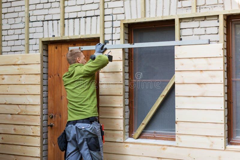 Pracownik wznawia starą cegła domu fasadę z nowymi drewnianymi deskami fotografia stock