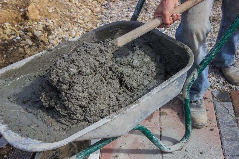 Pracownik z betonowym moździerzem w wheelbarrow 3 obrazy royalty free
