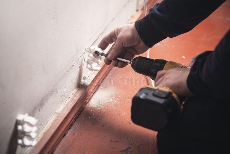 Pracownik z cordless śrubokrętem przekręca śrubę w ścianę zdjęcie stock