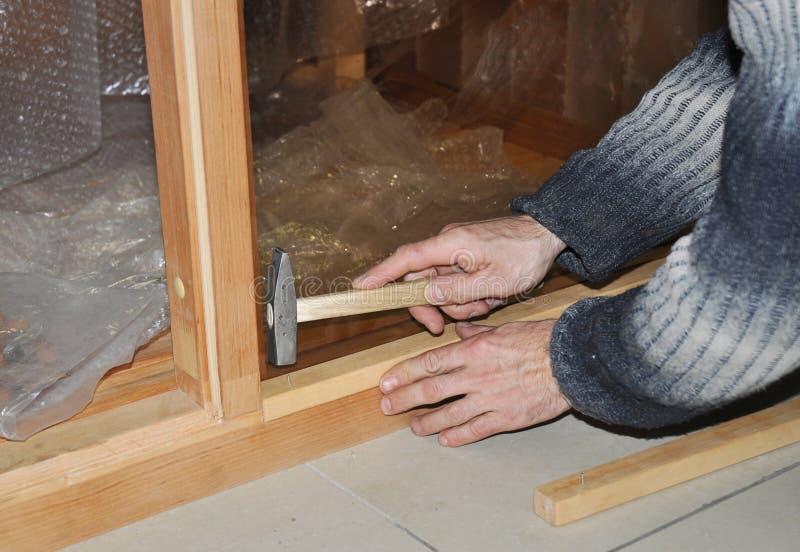 Pracownik z młota i gwoździa remontowym szklanym drzwi obraz royalty free