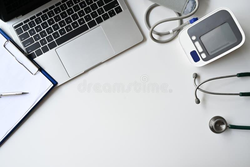 Pracownik z najwyższym widokiem przy stole z laptopem, ciśnieniem krwi, stetoskopem z klawiszem i piórem obraz royalty free