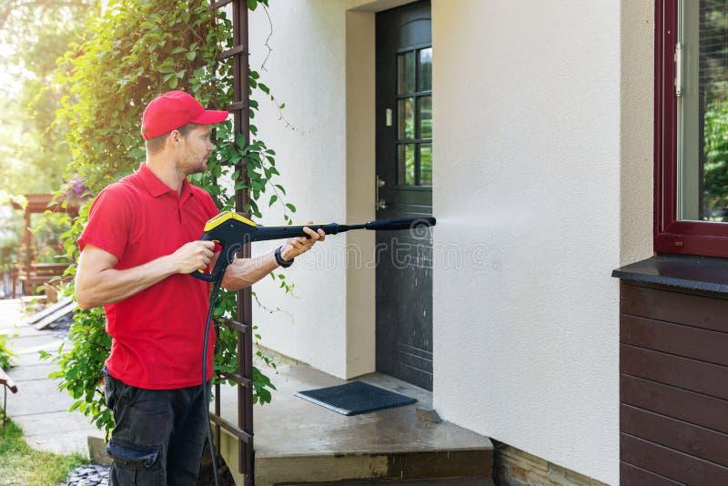 Pracownik z wysokość naciska płuczki cleaning domu fasadą obraz royalty free