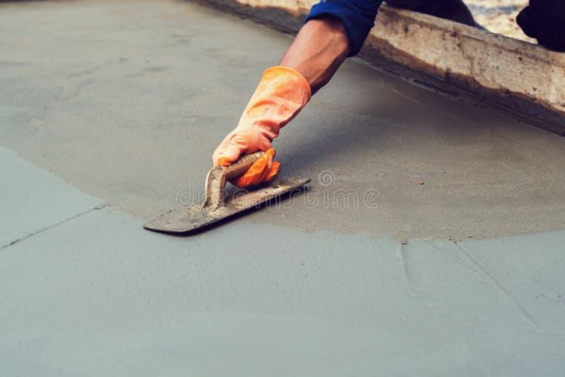 pracownik zrównuje betonowego bruk dla mieszanka cementu przy budową obraz royalty free
