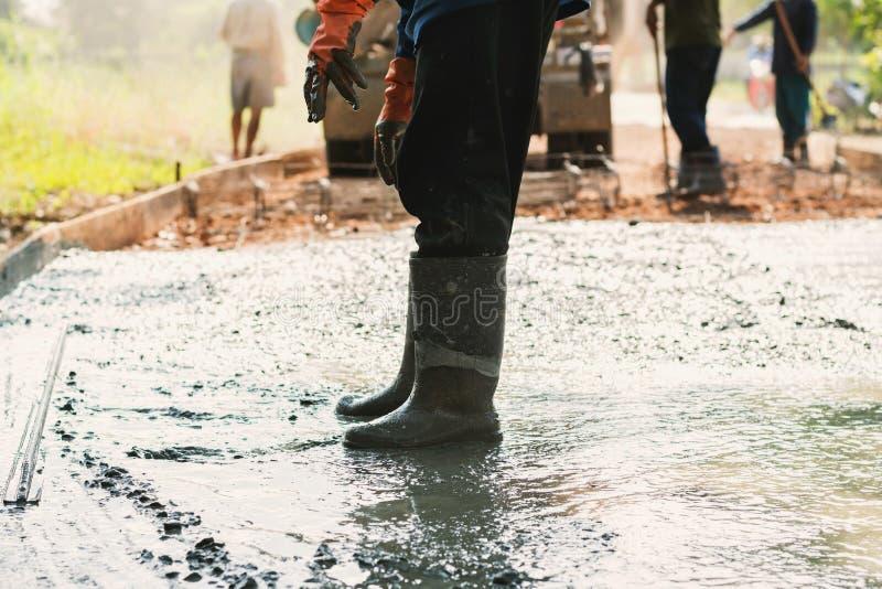 pracownik zrównuje betonowego bruk dla mieszanka cementu przy budową fotografia royalty free