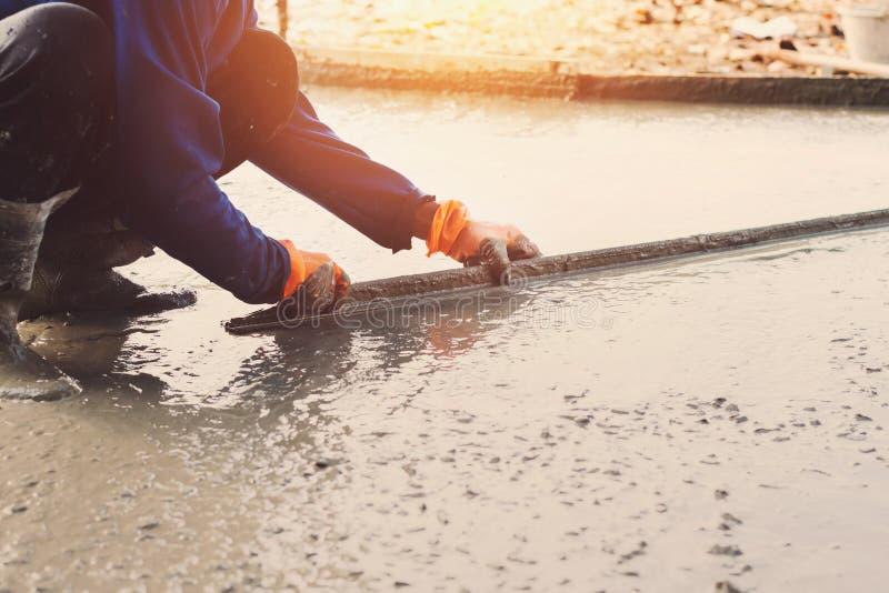 pracownik zrównuje betonowego bruk dla mieszanka cementu przy budową zdjęcie stock