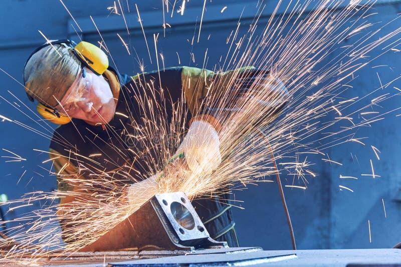 Pracownika śrutowania spawki szew z ostrzarz iskrami i maszyną obrazy stock