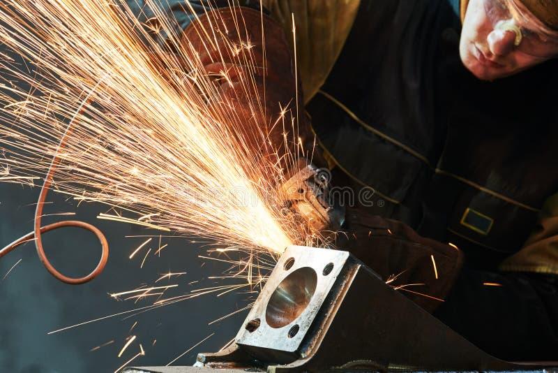 Pracownika śrutowania spawki szew z ostrzarz iskrami i maszyną obraz royalty free