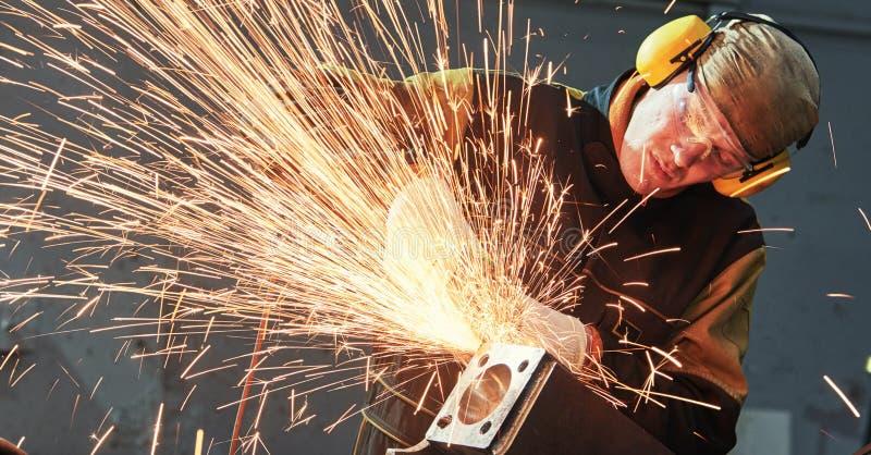 Pracownika śrutowania spawki szew z ostrzarz iskrami i maszyną zdjęcia royalty free
