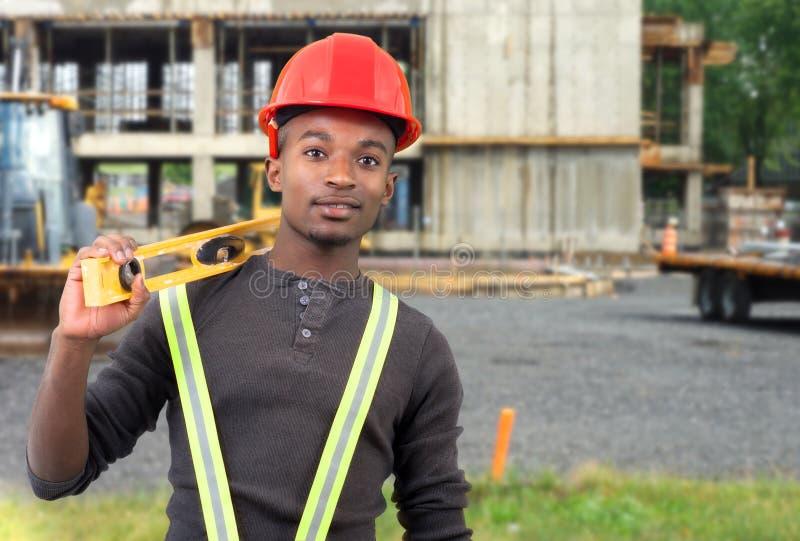 Pracownika budowlanego mienia pozioma narzędzie z czerwonym zbawczym kapeluszem obraz royalty free